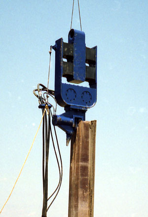 "The 1400, driving sheeting for a creosote plant environmental remediation in Chattanoga. The 1400 incorporated many of the features of the 400, including the curved eccentric case (which was mated to the 7"" clamp.) The original suspension was an H-beam, but this proved too light for bias weight, and was replaced by the cast unit shown."