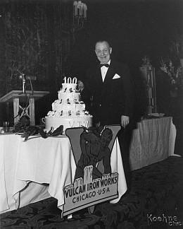 """His 1908 prep school annual from the Tome School said that """"Chet has beans in his bonnet,"""" but on this night Chester Warrington, President, had good reason for them. Here he stands next to the celebration cake and the """"V-Man Logo"""" that was Vulcan's trademark."""