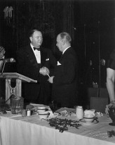 Homer Livingston, Present of the First National Bank of Chicago, passes the podium to Chester Warrington, President of Vulcan.