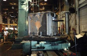 "A Vulcan 560 ram being machined by the Giddings and Lewis ""floor"" horizonal boring mill in 1993 (probably for Hyundai.) Boring mill capacity was the most important machining capability of the Chattanooga facility, as it was the hardest to procure elsewhere. Strolling down the aisle at the left is John Gourley, Vulcan's last plant manager for the 2909 Riverside Drive facility. He combined an affable nature with a superb command over manufacturing processes and costs to be the best plant manager Vulcan ever had at the Chattanooga facility."