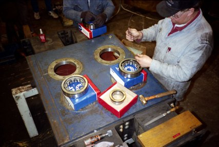 Rebuilding the 2300L case at PACO in Seattle, Washington, in 1991. The cylindrical roller bearings are being prepared for insertion in the case. Because of the continuously changing direction of the dynamic force, it is necessary to use an interference fit between the bore and the outer race. PACO's preferred method was to use dry ice to shrink the outer race and then lower it using a wire tied to the roller cage, a method Vulcan adopted for its own assembly.