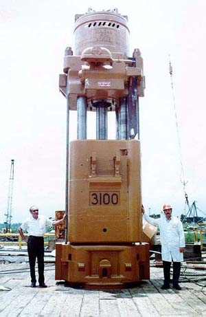 Proud of a job well done: Jesse Perry (left) and Norris Tremmier stand in front of a 3100 hammer they have just completed assembing in a customer's own yard. The 3100 hammer was the last 3' stroke hammer Vulcan produced for the offshore market; compared to the 560 with the same energy, it was heavy and drove the piles no better, if as well. Although Vulcan could assemble any hammer in or near the Chattanooga factory, field assembly was practical as the hammer was easier to ship in pieces, and when delivery was tight (which it almost always was) it speeded up the process. It also gave Vulcan's field personnel a chance to give a service school to the customer's people. With the demise of practical rail transport and the problems of trucking such a large piece, by the 1990's field assembly of offshore hammers became the norm.