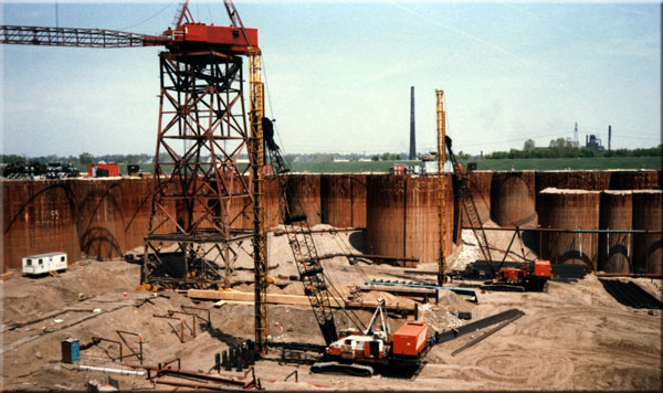 "Working in the dry, a Vulcan 512 drives the foundaton H-piles for the Lock and Dam 26 replacement near Alton, Illinois, in April 1986. The contractor was S.J. Groves. Cellular cofferdams are probably the most massive ""temporary"" structure used in construction. Although they are massive and look very rigid (especially in the view on the right,) they are in reality giant steel bags filled with pervious fill."