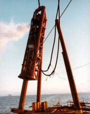 Vulcan 560 driving piles for a simple four-pile platform; Santa Fe was the contractor. This photo is interesting in several ways. It shows how the platform is used as a template. It also shows the batter of the piles; this was typical offshore. The operator is leaning the hammer properly so that the wear of the columns is more evenly distributed. Notice too the pile partially driven on the right; the flared pile head is due to premature refusal and brooming during driving, a testament to the punishment both hammer and pile experienced offshore.