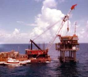 """After the piling was complete and the piles grouted to the jacket, the actual superstructure of the platform was installed. With the long work season in the Gulf and other tropical and sub-tropical regions, the superstructure was brought out in modules and assembled as shown below. Again the North Sea's hurried schedules forced the development of bringing out the entire superstructure in one piece and setting it on the jacket; this more than anything drove the construction of the very large derrick barges by McDermott and Heerema in the late 1970's and early 1980's. The superstructure had to be as light as possible, not only for lifting but for the structural economy of the platform. The question, """"too much weight topsides?"""" was more than a personal one for designers of conventional platforms."""