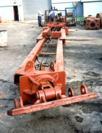 Transition to hydraulics: a cable spotter in Vulcan's facility in the early 1990's, a part of Vulcan's nascent used equipment efforts. In the front is the connection to the leaders, the back to the crane. The spotter is hinged at the rear so that it can move up and down; at the front it is set up to allow the side motion of the leaders as well.Completely hydraulic spotters have displaced cable and moonbeam alike. Also, some leaders are able to move vertically relative to both the boom point and spotter connections. These are very useful for driving piles that are well below the crane, such as is common with railway applications.