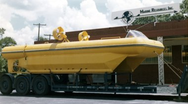 "Vulcan: The Offshore Experience Without a doubt the most intriguing ""special product"" Vulcan's West Palm Beach facility produced was the Construction Assistance Vehicle (CAV). The purpose of this was to provide an underwater craft to transport personnel and materiel during underwater construction. The CAV was capable of transporting one U.S. Ton (2000 lbs.) at a speed of 2 knots. It was intended to be manufactured using ordinary materials and fabrication techniques. Vulcan fabricated the hull for the U.S. Navy and loaded it out for shipment 29 November 1969. Below: on the trailer, ready for transport to California. An aft view of the CAV. A better view of the deck. Once in California, it was fitted out with its propulsion system and prepared for testing. Below, as completed and ready."