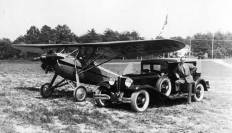 Chet Warrington with his two livelihoods, cars and airplanes. The airplane is a Davis, for which he was a dealer. He was also a dealer for Cord/Auburn/Duesenberg automobiles. Photo taken at Congressional Airport in Maryland.