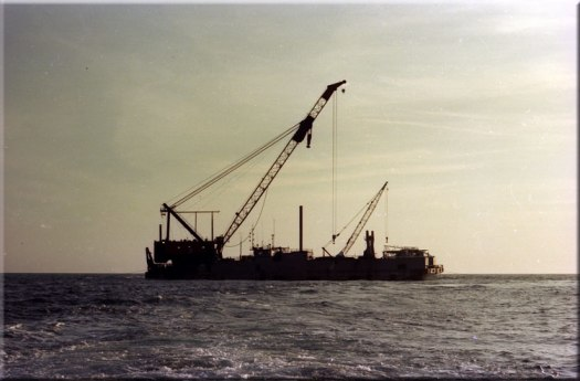 "A key element in platform installation: the derrick barge. The derrick barge shown below was a step forward from the construction barges used for bridges and the like, and certainly the spud-type barges such as is shown here. The flat-bottomed construction was very suitable for conventional platforms, both because of their size and the areas where they were the most suitable. The demanding conditions of the North Sea inspired the development of the semi-submersible self-propelled barges, which eventually became the state of the art in the field. Note that there is both the main installed crane on the barge and a smaller mobile deck crane. If carelessly handled, the latter could and did end up ""in the drink."""