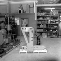 The Universal Backhoe Adapter at the Special Products Division, where it was manufactured. The hammer is laying on the pallet, and the adapter is upright, bolted to the hammer. Into the slots are welded bushings for the pins which affixed the assembly to the backhoe or excavator. The bushings were custom fitted into the slots for the proper position.
