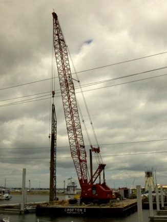 "An example of swinging leaders in use. The concrete piles are being driven for a marina in Norfolk, VA, September 2009. The leaders are suspended from the crane and are hanging from the hook block. There is an additional line for the Vulcan hammer as well. the ""headache ball"" immediately to the left of the leaders is a useful part of the rigging. Although the hammer is heavy, when the hammer is disconnected from the cable, if there is no weight, the weight of the cable behind the boom point will pull the cable back through the boom point. To remedy this problem requires one of two solutions: Lay the boom down and rethread the cable. Send someone up the boom to pull the cable through, a very dangerous operation and one that should be avoided at all costs (although this webmaster has seen it done.) The headache ball, in reality, saves many other headaches on the job."