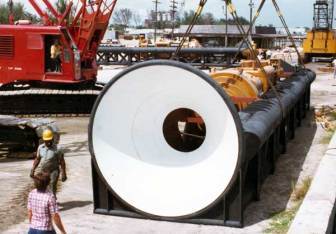 A hammer package being shipped from the Port of Palm Beach. The stabbing bell makes it easier for the crane operator to guide the pile to the pipe cap. They're faint, but one can see the concentric rings of the adjustable bell; these could be removed or added back for different sizes of pipe. The black with white bell was the standard Vulcan colour scheme for its leaders, although the action shots make it clear that paint didn't last too long offshore. Shipping the hammer in the leaders was a sensible option, especially since deck cargo is charged both by weight and volume. Note yet another package in the background.