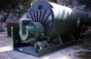 "The prime mover for the system, in this case a Johnston boiler. Steam was the original method for powering Vulcan hammers, but the maintenance hastened the switch to air for onshore hammers. For offshore hammers, though, steam remained the motive fluid of choice for many years. Although onshore contractors generally used upright, water-tube boilers (Raymond was the best example of this,) the Scotch marine, fire-tube type is really better, as it has more reserve of steam to handle the intermittent flow requirements of the hammer. Vulcan's customers generally purchased their own boilers, but every now and then Vulcan would sell a ""package deal"" to an end user. This was the case in Vulcan's first sale to the People's Republic of China. Ten years later they would do the same thing with the Korean contractor Daelim, and their new Johnston boiler is shown here."