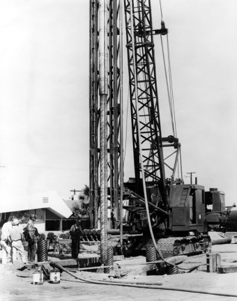 "The Vulcan Expanding Mandrel, probably having just been removed from the shell pile it has just driven at a job in Indio, California, near Palm Springs. At the start of driving, the shell is hoisted into the leaders and the mandrel lifted above the head of the shell and inserted into the shell. In the event that the leaders weren't long enough for both mandrel and shell, a ""doodle pipe"" could be used. This is a pipe slightly larger than the shell's outside diameter, driven at one place on the jobsite and completely clear of internal soil. A shell would be first inserted into the doodle pipe, then the mandrel lowered into the shell and expanded, and finally the assembly would be lifted out of the doodle pipe and positioned for proper installation."