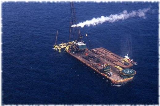 A spectacular photo taken from a helicopter shows a Vulcan offshore hammer at work from a J. Ray McDermott barge in 1976. The barge layout is typical, with the crane on one end, deck in the middle, and heliport on the other. A supply barge and tugboat are pulled up on the barge's starboard. The platform is off the bow of the barge, but it could also be off of the beam as well.