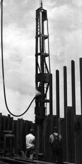 A Vulcan differential acting hammer driving sheet piling using the staggered procedure, i.e., driving alternating sheeting and then coming back and driving those skipped. Note the use of stub leaders. Merritt-Chapman-Scott was the contractor.