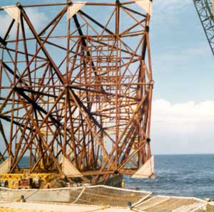 Once the jacket was finished, it was placed on a barge and floated out to the spot in the ocean where it was intended to be installed. Below is a view of the jacket and barge below it as they approach the derrick barge (the construction barge used to actually complete the construction of the platform.) The triangular plates on the bottom of the platform are mud mats; they prevent the platform sinking into the soft ocean floor after it is upright and resting on the bottom. Virtually all platforms are tapered to the top, as the moments from wind and wave action are the greatest at the ocean floor, the platform itself being a giant cantilever.