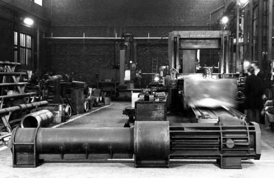 "A view of Nilens' shop in Vilvorde. Vulcan personnel, be they field service people or corporate executives, and no matter how ""exotic"" the destination, spent a lot of time in machine shops and foundries. In the front is a cylinder in process for an N46 hammer; in this case, the cylinder is one piece. (Most Nilens hammers used a two piece cylinder.) The integration of fabricated and cast pieces (detailed below) had no parallel with Vulcan equipment. In the back is the boring and planing equipment that is essential to the manufacture of pile driving equipment."