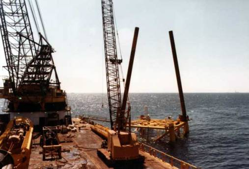 """Once the jacket was set, pile driving could begin. The set platform became a template for the piles, which were driven through the legs. Below is a good view of a four-pile platform with two of its piles """"stabbed"""" through the legs. Once driven, these would hold the platform to the sea bed."""