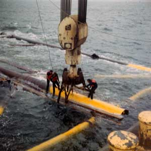 "Once the jacket had arrived at the site, the legs were flooded and the jacket sank upright to the sea floor. Setting the jacket could be a trying task, as the photo below and the one to its right can attest. Sometimes it was necessary for the barge (or more than one) to pick up and move the jacket, as it would be ""off station."""