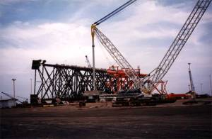 Ready to be floated out, a conventional platform sits behind a yard crane in McDermott's Batam, Indonesia yard in January 2000.