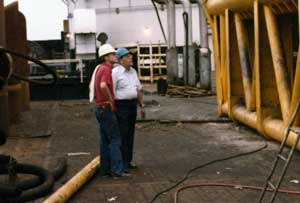 Not all service calls were carried out by the field service personnel: Pem Warrington, Executive Vice President (in the red shirt) talking with Art Anderson, metallurgist with Blaw-Knox foundry during a field repair of a 5150 hammer for Brown and Root.