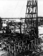 A skid rig with a Vulcan hammer driving steel Monotube piles for a blast furnace. Skid rigs were the most common way of handing pile driving equipment until the wide acceptance of modern crawler cranes for this purpose. Monotube piles are still in common use.