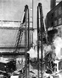 """Two rigs at once speed up work for Spencer, White and Prentis, one of the pioneering firms in deep foundations installation. In 1936 Lazarus White reported that """"I read some papers last night where some of these pile driving formulas were derived, and the result was that my sleep was very much disturbed."""" This didn't stop Vulcan from putting Engineering News charts and tables in their literature for many years."""