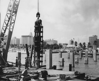 "A Vulcan 020 being prepared to drive square concrete piles for the original Dodge Island bridge, 1963. In the background is downtown Miami. Another photo from this job graced the cover of Vulcan Bulletin 68K for the single-acting onshore hammers. Note the use of the ""offshore"" type stub leader."