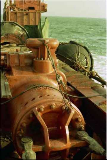 An overview of suspension cables, which became the accepted method of suspending Vulcan offshore hammers from the offshore type leaders. Onshore hammers used sheaves to raise and lower the hammer, but this was not applicable to a stub leader. Originally Vulcan intended for its customers to use the bar head (the bar is at the centre of the hammer on the 560 hammer on the left, between the two spelter sockets) and use a clip-secured wrap between the leader and the hammer. The suspension cables, attached in pairs to both hammer and leaders, proved a cleaner and more reliable method of doing this. In these photos spelter sockets are shown, but Vulcan furnished (when the customer needed them) swaged sockets. In either case the hammer was given sufficient leeway to ride down with the pile it was driving and give the crane operator the opportunity to keep the leader moving with the hammer without the cables becoming tight.