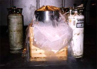 The first step is to build an insulated box with a hole in the centre and surround the hold with liquid nitrogen (shown below, with the large diameter of the point sticking out of the top.) When cooled enough, the point is then taken out and very slowly lowered into the ram (as shown to the left,) making sure it is straight.