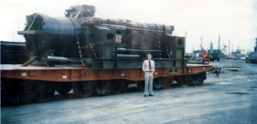 "Vulcan's Executive Vice President, Pembroke M. Warrington, in front of a Vulcan 5150 for his customer, Brown and Root, April 1979. It arrived from Chicago on the rail car, waiting to be offloaded. Equipment of this size was almost commonplace in the offshore oil industry. Twelve years later Pem stated that Vulcan had been ""the experience of a lifetime,"" and equipment like this was a large reason why that was so."