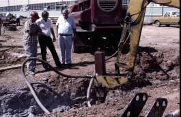 Bustin' rocks: the Vulcan DGH-100 hammer on a backhoe adapter during Vulcan's plant expansion in 1979. Left to right watching the hammer: (in hardhat) Gene Daniels, Vulcan's Construction Manager for the project; Kurt Winters, Onshore Sales Manager, and W. Calvin Bridges, Executive Vice President.