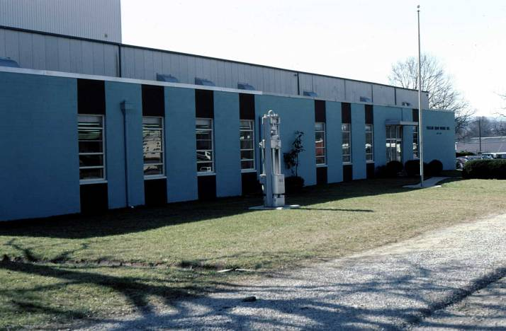 Vulcan's office, Spring 1980. Behind the office is the old plant, and behind that the new expansion, still under construction. The hammer in the front is the Vulcan #3, which had gone out of production many years before but was revived (with changes) by Pile Hammer Equipment in 2008. The office itself had already expanded; the area on the left was the Engineering area, added the previous year.