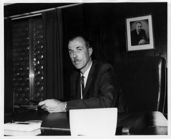 Henry Warrington at his desk. Behind him is his father Chet's photo. Chet left a spacious legacy which was hard to escape from.