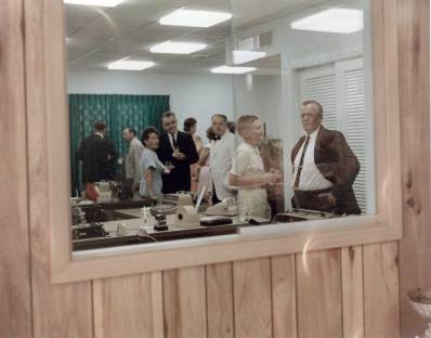 "Looking through the receptionist's window into the secretarial pool office. Behind the glass, facing right and holding a drink is a very young Pem Warrington, later Executive Vice President, who would ""office remotely"" from the Houston facility from 1978 to 1992. He is taking with Capt. Jim North, whose nephew Bob would work as a sales manager for Vulcan in the 1970's."