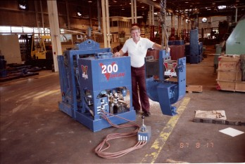 "Vulcan's first high-frequency vibratory hammer, first named the 200, later renamed the 400. the photo includes the exciter (with the soon to be replaced motor guard design,) open power pack and air remote control. Being the ""model' for the hammer is Kurt N. Winters, Vulcan's Onshore Sales Manager and later principal in HPSI."