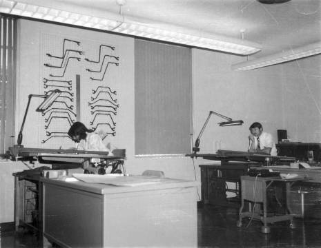 The drawing board(s) in Chattanooga. On the wall are sheet pile sections, cut from actual sheet piling and used to lay out sheet pile caps. In front of the sheet piling are two draughtsmen who started at Vulcan in the early 1970's. On the left is Michael Steven Alexander, who worked for Vulcan until he left during the downturn in the first part of the 1980's. On the right is William C. Harrison, who went off the board to become Vulcan's Field Service Representative in 1981.