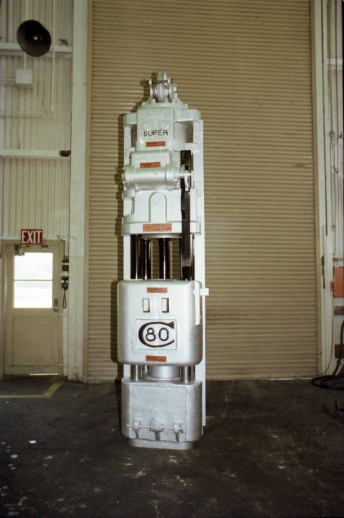 "Vulcan 80C cable hammer, S/N GH-1070, taken 17 January 1979 at the Chattanooga plant. Vulcan was relatively late in the life of the product line in putting cables on the differential-acting hammers, and when it did the ""pockets"" (which you can see on either side of the cylinder just below the steam chest) made it impossible to jack the cables. Both Raymond and Pile Hammer Equipment had better methods of cabling the Super-Vulcan hammers."
