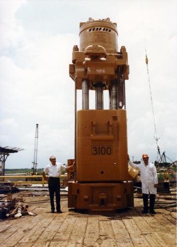 A job well done: Jesse Perry (left) and Norris Tremmier stand beside the 3100 on the deck of McDermott's DB 8 with the completed 3100, July 1975.