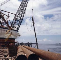 A side view of a Vulcan 040 driving pile offshore in the Gulf of Mexico from Ingram's DB 3, 1966. Note the batter (angle) of the pile. Batter conditions were standard for offshore piling and it was one reason why the environment was so hard on the equipment.