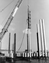Misener Marine using a Vulcan 010 hammer in a stub leader with a template aligning the concrete piles (as can be seen at the water line) at Port Canaveral, November 1974.