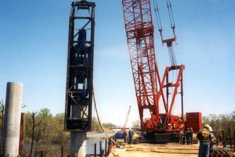 Vulcan 535 hammer driving piles near Trenton, NJ, during the mid-1990's. The contractor was Bellezza. A template was used (below the bottom of the photo) to align the concrete cylinder pile.